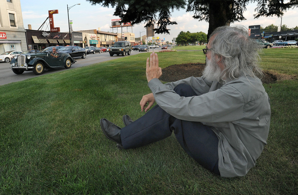 . Jerome Lothamar of Detroit, Mich., waves hi to a passing motorist who was driving a classic car, along northbound Woodward near the Nine Mile Road intersection.  Lothamar says he comes out every year to watch the Dream Cruise.  Photo taken on Thursday, August 19, 2010, in Ferndale, Mich.  (The Oakland Press/Jose Juarez)
