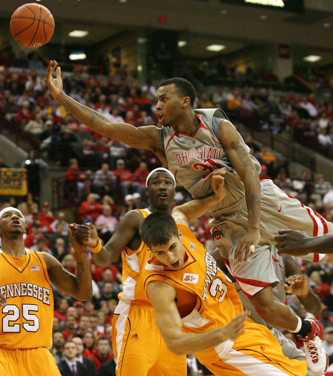 . Ohio State\'s Daequan Cook (31) charges into Tennessee\'s Ryan Childress (34) during the second half of a college basketball game Saturday, Jan 13, 2007, in Columbus, Ohio. Tennessee\'s Josh Tabb (25) and Wayne Chism, rear center, look on. (AP Photo/Terry Gilliam)