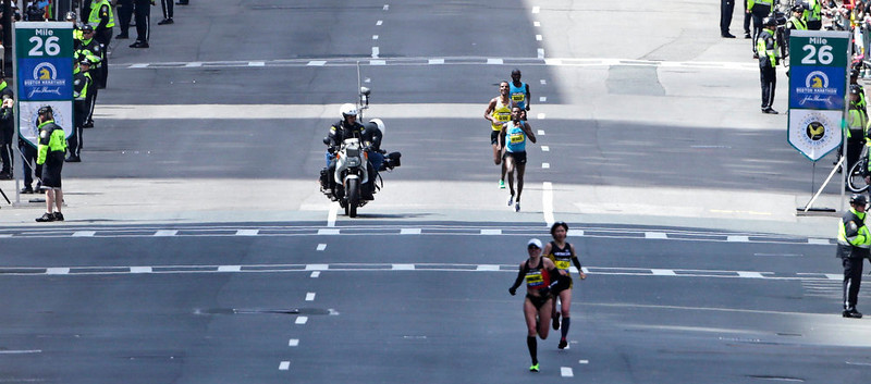 . A motorcycle camera crew photographs the lead men\'s finishers as they pass the 26th mile marker, which was dedicated to the victims of the Sandy Hook Elementary School shooting in Newtown, Conn., during the 2013 running of the Boston Marathon in Boston, Monday, April 15, 2013. (AP Photo/Charles Krupa)