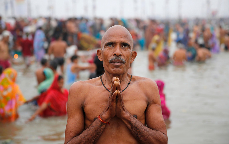 ". An Indian Hindu devotee offers prayer after taking a holy dip at the ""Sangam,\"" the confluence of the Ganges and Yamuna,and mythical Saraswati river, during the annual traditional fair \'Magh Mela\' in Allahabad, India,  Wednesday, Jan. 29, 2014. Hundreds of thousands of devout Hindus are expected to take holy dips at the confluence during the astronomically auspicious period of over 45 days celebrated as Magh Mela. (AP Photo/Rajesh Kumar Singh)"