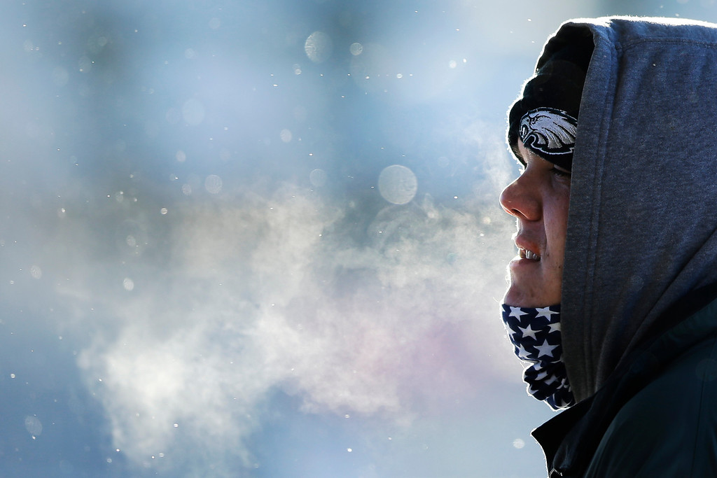 . A commuter exhales in freezing tempters in the aftermath of a snowstorm Wednesday, Jan. 22, 2014, in Philadelphia.  A winter storm stretched from Kentucky to New England and hit hardest along the heavily populated Interstate 95 corridor between Philadelphia and Boston.   (AP Photo/Matt Rourke)