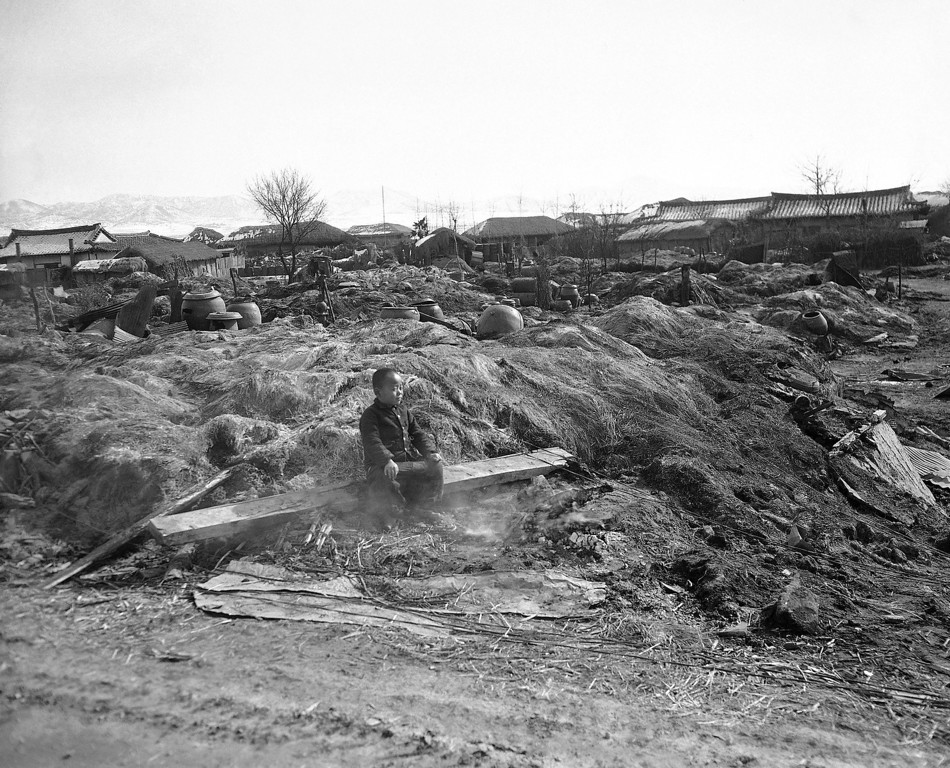 . A Korean waif sits in smoldering ruins of his home destroyed by fire in the Suwon area on Feb. 3, 1951 as allied troops burned dwellings which might provide shelter for red troops. Native water jars are the only possessions recognizable in ruins of other native homes in background. (AP Photo/Jim Pringle)