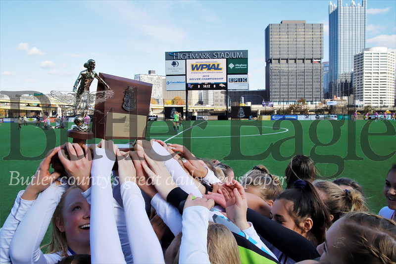 North Catholic girls soccer players raise the AA WPIAL trophy after beating Yough 1-0 in double overtime at Highmark Stadium in Pittsburgh Saturday. Seb Foltz/Butler Eagle