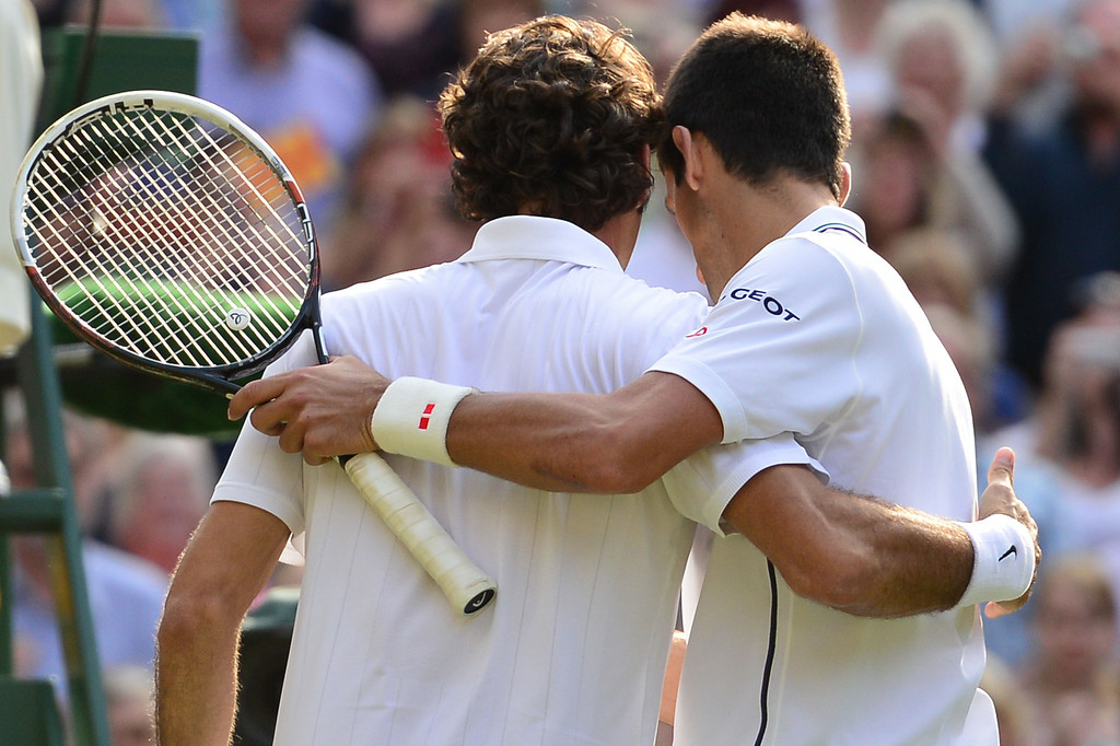 . Serbia\'s Novak Djokovic (R) hugs Switzerland\'s Roger Federer after the former won their men\'s singles final match on day thirteen of  the 2014 Wimbledon Championships at The All England Tennis Club in Wimbledon, southwest London, on July 6, 2014. Djokovic won his second Wimbledon title and seventh career major with a 6-7 (7/9), 6-4, 7-6 (7/4), 5-7, 6-4 victory over Roger Federer Sunday, shattering the Swiss star\'s dream of a record eighth triumph in a titanic struggle.   CARL COURT/AFP/Getty Images
