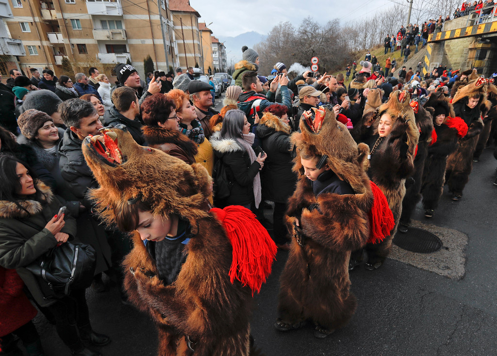 . In this Saturday, Dec. 30, 2017 picture people watch an annual bear parade in Comanesti, Romania. Hundreds of people descend on the sleepy northern Romanian city of Comanesti every year dressed head to toe like bears, in costumes made from real fur, with the heads attached. (AP Photo/Vadim Ghirda)