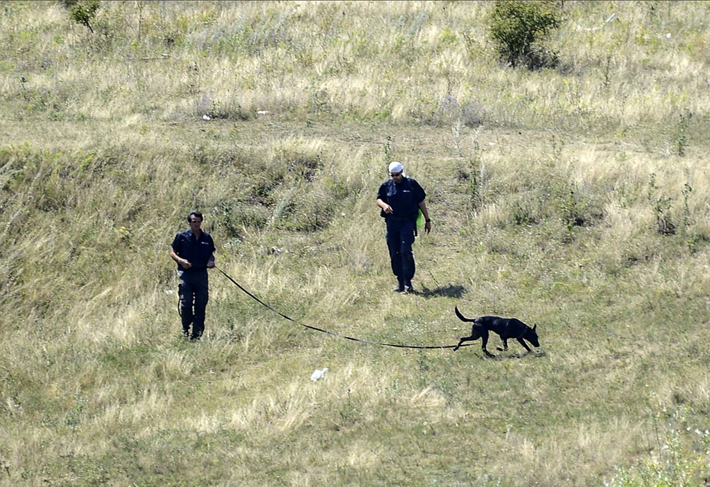 . Experts examine the area of the Malaysia Airlines Flight 17 plane crash in the village of Hrabove (Grabovo), some 80km east of Donetsk, on August 2, 2014. Shelling on August 2, 2014 forced international experts to abandon part of the crash scene of the downed Malaysia Airlines jet in east Ukraine as sniffer dogs working elsewhere on the vast site helped uncover the remains of more victims. 298 people were killed when the Malaysian airliner was shot down over Ukraine on July 17. AFP PHOTO/ BULENT KILICBULENT KILIC/AFP/Getty Images