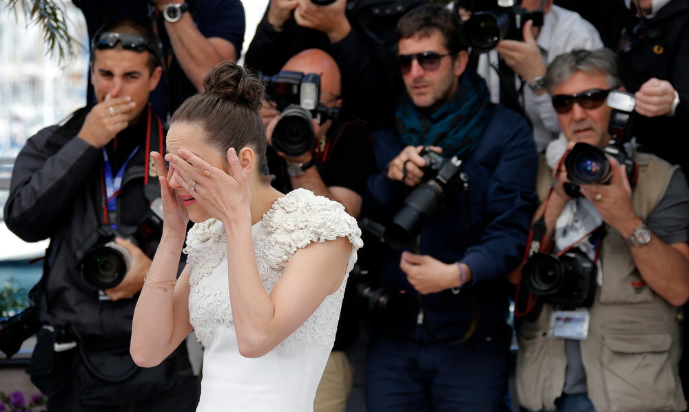 . Actress Marion Cotillard rubs her eyes as she poses for photographers during a photo call for the film The Immigrant at the 66th international film festival, in Cannes, southern France, Friday, May 24, 2013. (AP Photo/Lionel Cironneau)