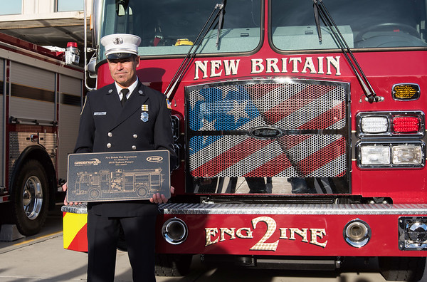 11/14/18 Wesley Bunnell | Staff The New Britain Fire Department unveiled three new fire trucks on Wednesday afternoon during a ceremony at their Beaver St headquarters. Captain Gary Turek holds a plaque of Engine 2 while posing for photos.