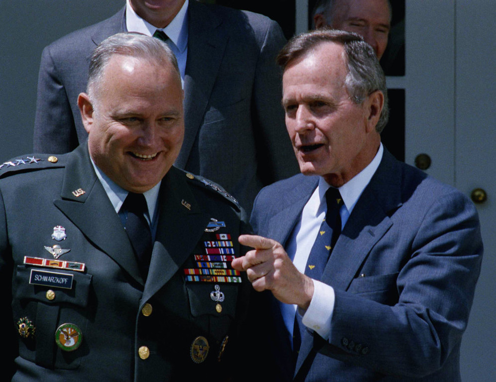 . President Bush gestures while posing for photographer with Gen. Norman Schwarzkopf in the White House Rose Garden, April 23, 1991 in Washington. Schwarzkopf, just back from commanding the U.S.-led military victory over Iraq, joined the President for lunch at the White House. (AP Photo/Marcy Nighswander)