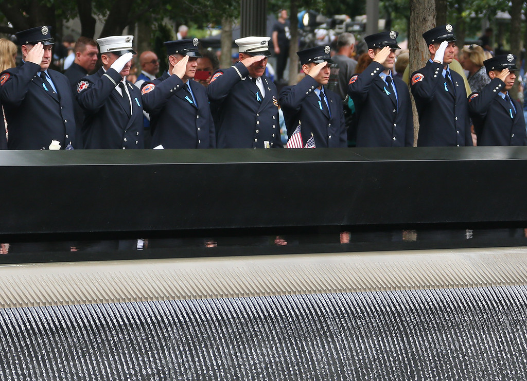 . Firefighters including some from Engine Company 217, pay their respect to the fallen colleagues at South Tower Pool during memorial observances on the 13th anniversary of the Sept. 11 terror attacks on the World Trade Center in New York, Thursday, Sept. 11, 2014. (AP Photo/The New York Times, Chang W. Lee, Pool)