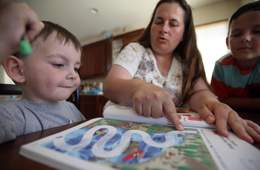 . Matthew Ouimet, 3, left, works on his motor skills with his mom Kristi, center, and brother Patrick, 9, at their home in Antioch, Calif., on Friday, May 23, 2014. (Jane Tyska/Bay Area News Group)
