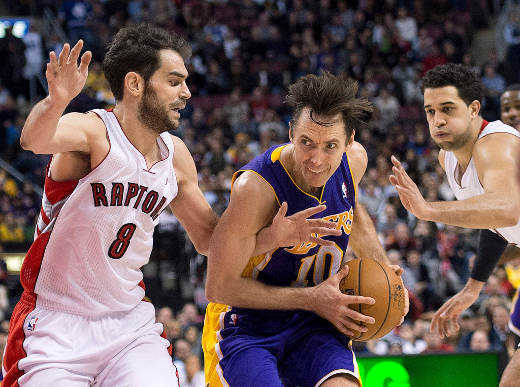 . Los Angeles Lakers guard Steve Nash, center, drives past Toronto Raptors guard Jose Calderon, left, and forward Landry Fields, right, during the second half of an NBA basketball game in Toronto on Sunday, Jan. 20, 2013. (AP Photo/The Canadian Press, Nathan Denette)