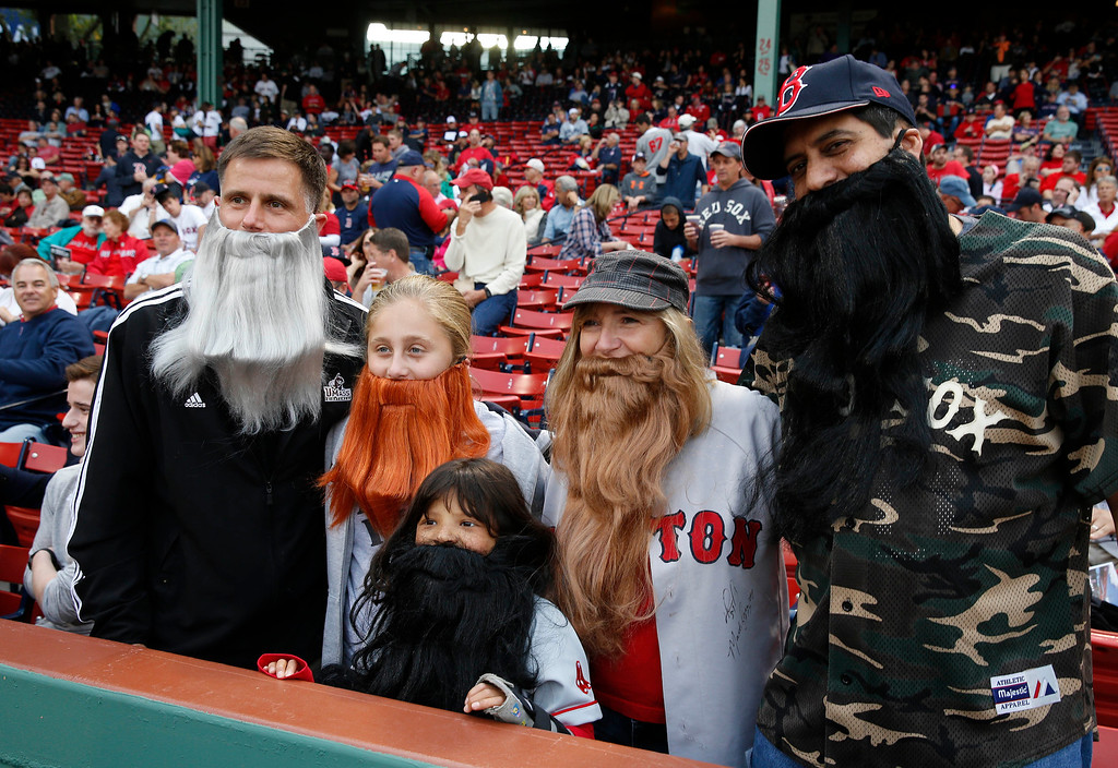 . From left, Silvio and Isabella Bonvini, and Laurie, Shauna and Chris Sperou, all from Marlborough, Mass., wear fake beards to honor the Red Sox, most of whom wear beards, before Game 2 of baseball\'s American League division series between the Red Sox and the Tampa Bay Rays on Saturday, Oct. 5, 2013, in Boston. (AP Photo/Michael Dwyer)