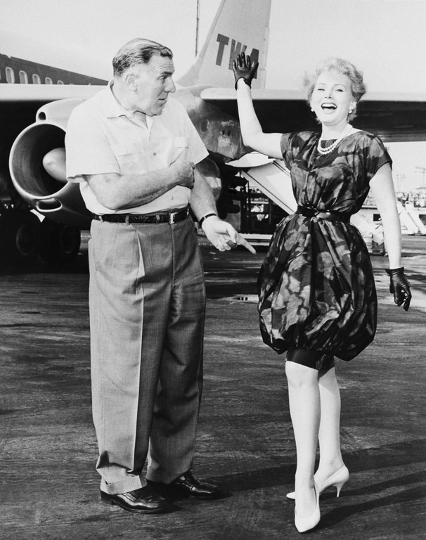 . Actress Zsa Zsa Gabor exhibits her latest choice in fashion styling at Idlewild Airport, New York City, on August 17, 1959.  She wears bell-shaped skirt which is hobbled just above the knee, along the lines of new Dior idea.     She posed before boarding TWA jet airliner for Los Angeles after trip to New York to make television pilot film.    At left is actor William Bendix.     (AP Photo)