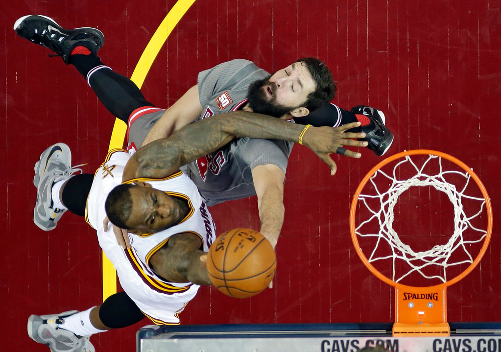 . Cleveland Cavaliers\' LeBron James, left, drives to the basket against Chicago Bulls\' Nikola Mirotic, from Montenegro, in the second half of an NBA basketball game Saturday, Jan. 23, 2016, in Cleveland. The Bulls won 96-83. (AP Photo/Tony Dejak)