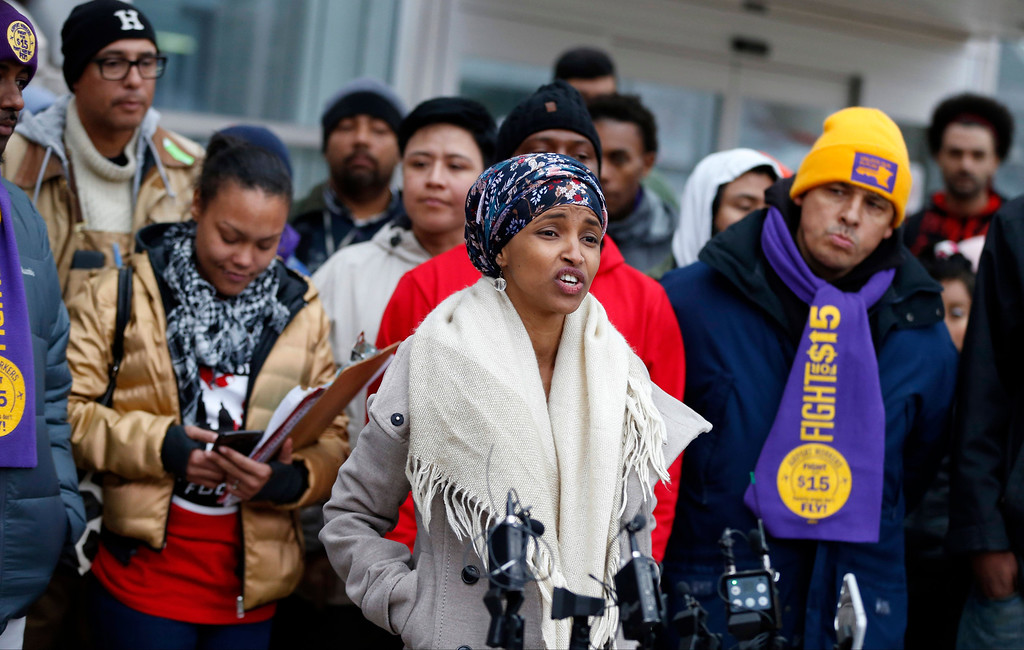 . Ilhan Omar, center, the first Somali-American elected to a state legislature, speaks during a rally Tuesday, Nov. 29, 2016, at the Minneapolis-St. Paul International Airport in Minneapolis, calling for $15 minimum wages. Those in attendance included airport workers. (AP Photo/Jim Mone)