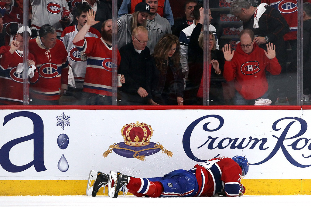 . Alexei Emelin #74 of the Montreal Canadiens lays on the ice after getting hit by Benoit Pouliot #67 of the New York Rangers during the third period in Game Two of the Eastern Conference Final during the 2014 Stanley Cup Playoffs at Bell Centre on May 19, 2014 in Montreal, Canada.  (Photo by Bruce Bennett/Getty Images)