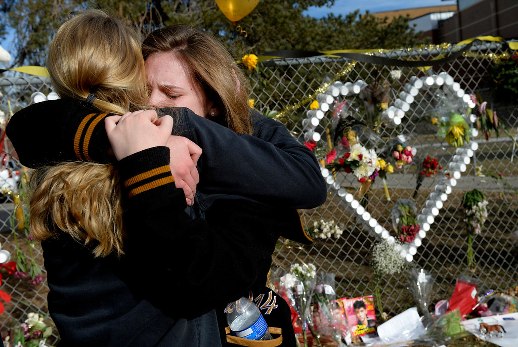 """. Senior Lily Boettcher, right, is comforted by graduate Joy Dafoe outside Arapahoe High School in Centennial, CO December 19, 2013. Seniors and Juniors returned to the school for two hour periods Thursday, Sophomores and Freshmen will return on Friday. Lily said, \""""it was good to be back in the school with everybody. I love my school so much. I couldn\'t ask for a better community. The victim from Friday�s shooting at Arapahoe High School, Claire Davis, 17, remains in critical condition. She was shot on Friday when classmate Karl Pierson opened fire in the school. The gunman died from a self-inflicted gunshot wound. (Photo By Craig F. Walker / The Denver Post)"""