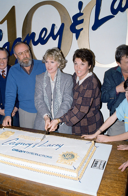 ". Actress Sharon Gless, center left, and actress Tyne Daly, cut cake surrounded by cast members and production crew celebrating the 100th episode of their TV-show ""Cagney and Lacey"" in Los Angeles Calif., Jan. 21, 1987. (AP Photo/Douglas C. Pizac)"
