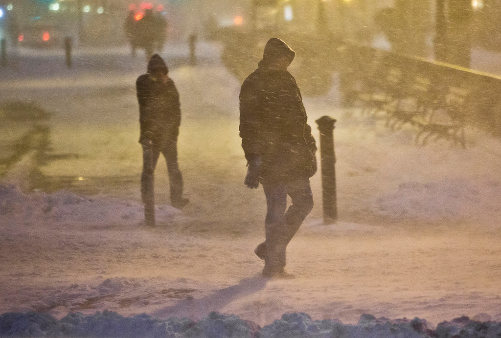 . Pedestrians walk through wind-swept snow in downtown Brooklyn, Monday, Jan. 26, 2015, in New York. More than 35 million people along the northeast corridor rushed to get home and settle in Monday as a fearsome storm swirled in with the potential for hurricane-force winds and 1 to 3 feet of snow that could paralyze the Northeast for days. (AP Photo/Bebeto Matthews)
