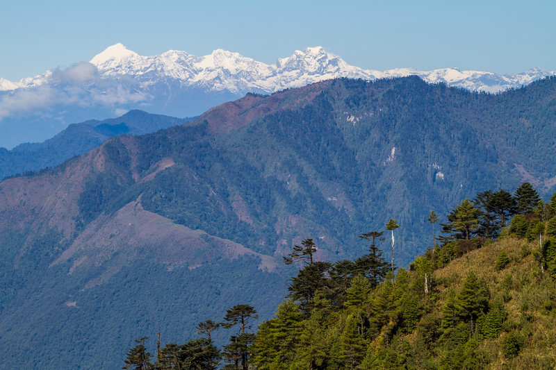 Distant Himalayan Peaks are seen from the roadside in rural Bhutan