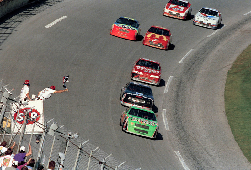 . Dale Jarrett, from Hickory, N.C., driving the Interstate Batteries Chevrolet, takes the checkered flag to win 35th running of the Daytona 500 at Daytona International Speedway in Daytona Beach, Florida on Sunday, Feb. 14, 1993. Following behind Jarrett is Dale Earnhardt, from Kannapolis, N.C., who finished second, and Geoff Bodine, from Chemung, N.Y., who finished third. (AP Photo/David Graham)