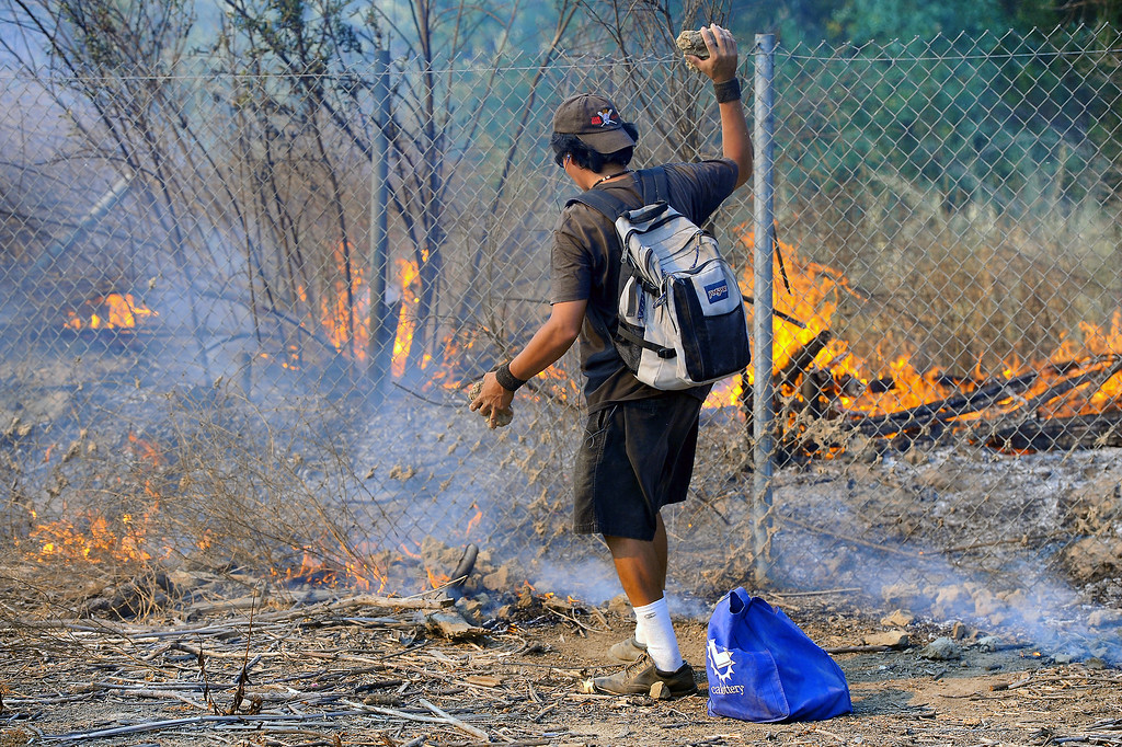 . A man tosses dirt clods on a brushfire in the Sepúlveda Basin, Friday, August 22, 2014. (Photo by Michael Owen Baker/Los Angeles Daily News)