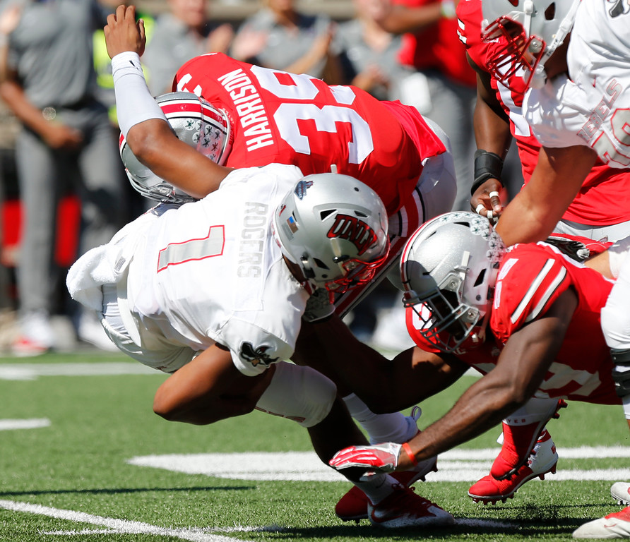 . Ohio State linebacker Malik Harrison, top, and defensive lineman Tyquan Lewis, right, sack UNLV quarterback Armani Rogers during the first half of an NCAA college football game Saturday, Sept. 23, 2017, in Columbus, Ohio. (AP Photo/Jay LaPrete)