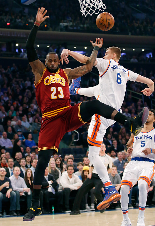 . New York Knicks forward Kristaps Porzingis (6) fouls Cleveland Cavaliers forward LeBron James (23) in the first quarter of an NBA basketball game at Madison Square Garden in New York, Wednesday, Dec. 7, 2016. (AP Photo/Kathy Willens)