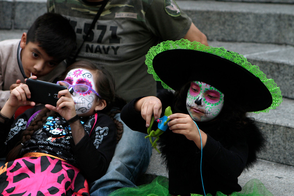 . Brother and sister, Orlando and Connie Rangel, and their cousin Valentina, entertain themselves as they wait for the start of the Gran Procession of the Catrinas, to mark the upcoming Day of the Dead holiday, in Mexico City, Sunday, Oct. 23 2016. The gran procession is one of many that will take place in Mexico City as part of the celebrations, culminating with visits to the graves of departed loved ones on Nov. 1 and 2. The figure of a skeleton wearing broad-brimmed hat was first done as a satirical engraving by artist Jose Guadalupe Posada sometime between 1910 and his death in 1913, to poke fun at women who pretended to be European by dressing elegantly and as a critique of social stratification. (AP Photo/Anita Baca)