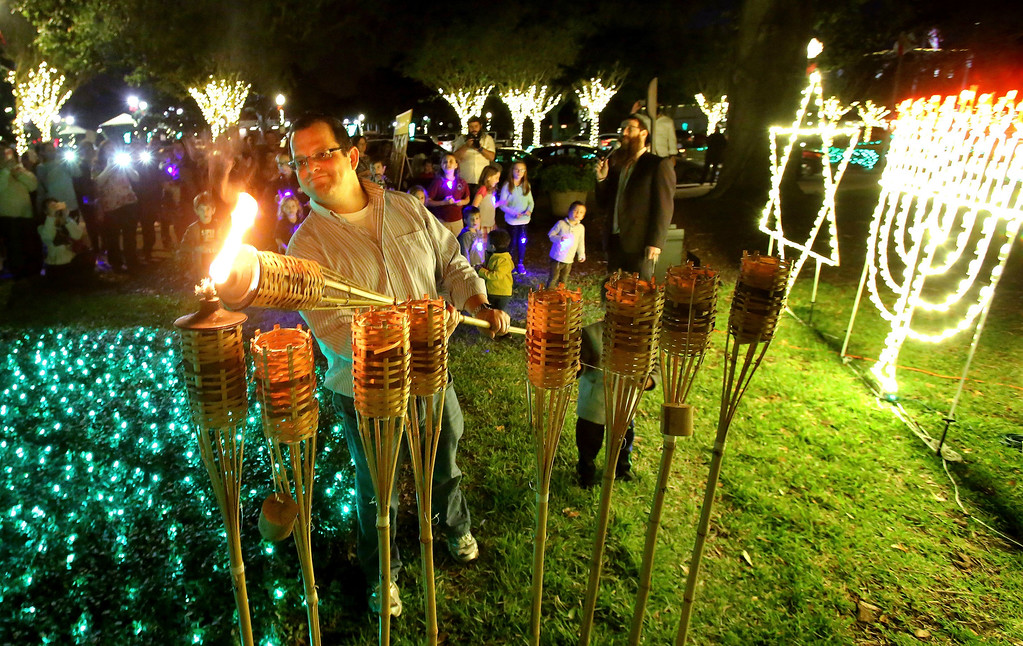 . Adam Rashkind of Winter Garden, Fla. symbolically lights the first candle of the eight days of Hanukkah as members of the central Florida Jewish community and residents of Winter Garden gathered for the first-ever Menorah lighting ceremony Tuesday, Dec. 12, 2017. (Joe Burbank/Orlando Sentinel via AP)