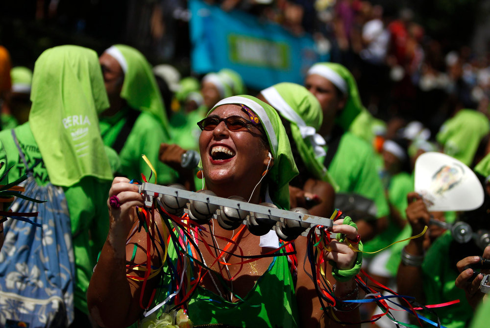Description of . Revellers play instruments during the annual block party known as \'Carmelitas\', one of the many carnival parties to take place in the neighbourhoods of Rio de Janeiro, February 8, 2013. REUTERS/Pilar Olivares