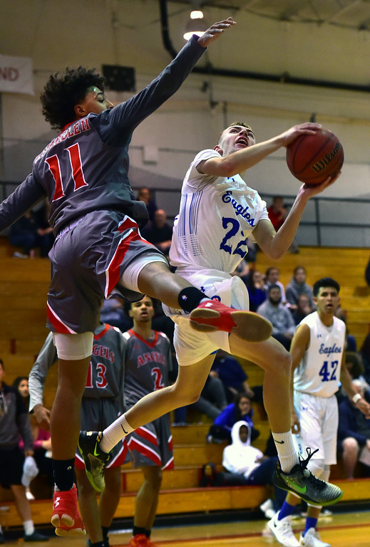 . Broomfield High School\'s Kip Mielke twists to the basket against Denver East\'s Kwane Marble II during their game in the Fairview Festival on Wednesday. For More photos go to bocopreps.com Paul Aiken Staff Photographer Dec 6 2017