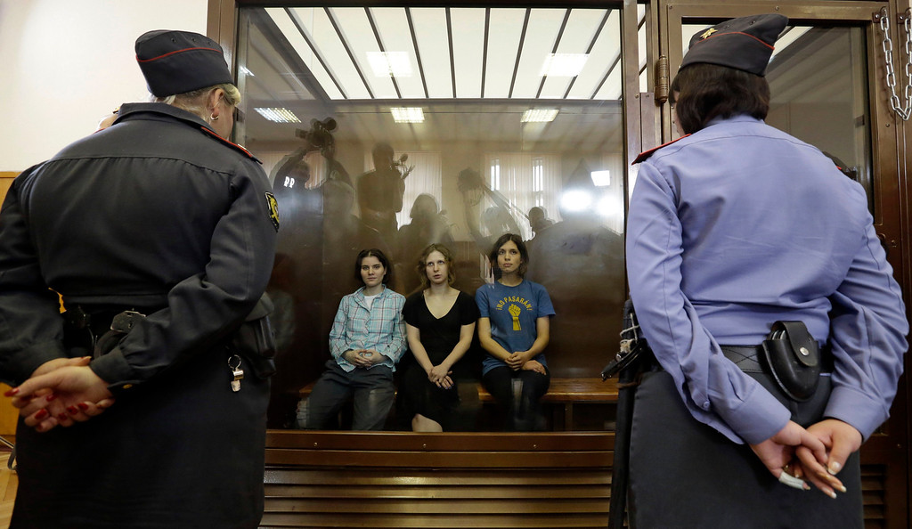 ". In this Aug. 17, 2012 file photo, feminist punk group Pussy Riot members, from left, Yekaterina Samutsevich, Maria Alekhina and Nadezhda Tolokonnikova sit in a glass cage at a court room in Moscow, Russia. The women, two of whom have young children, are charged with hooliganism connected to religious hatred. The case was widely seen as a warning that authorities will tolerate opposition only under tightly controlled conditions. T-shirt on right worn by Tolokonnikova is Spanish and translates to ""They shall not pass\"", a slogan often used to express determination to defend a position against an enemy.(AP Photo/Sergey Ponomarev, File)"