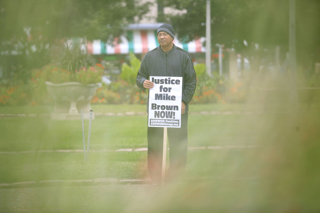 . A man holds a sign as he protest  the shooting death of Michael Brown on October, 11 2014 in St. Louis, Missouri. Civil rights organizations, protest groups and people from around the country were protesting the August 9 shooting of Brown, 18, which involved Ferguson Police officer Darren Wilson in the suburban town of Ferguson near St. Louis. AFP PHOTO/Joshua LottJoshua LOTT/AFP/Getty Images