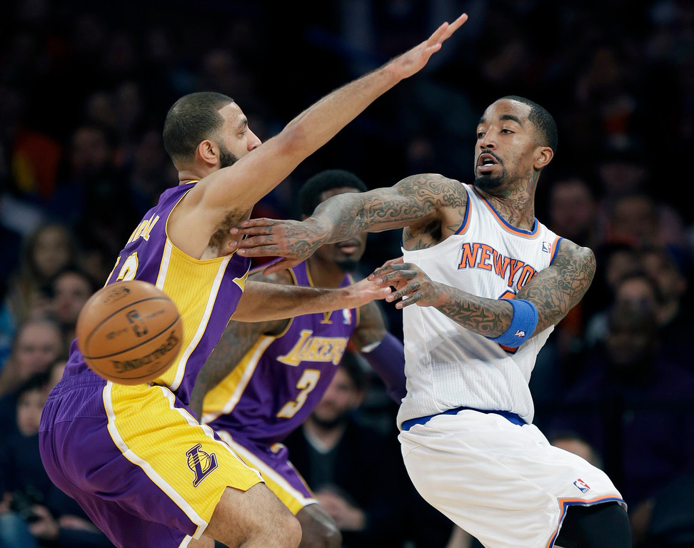 . New York Knicks\' J.R. Smith, right, passes around Los Angeles Lakers\' Kendall Marshall during the second half of an NBA basketball game at Madison Square Garden, Sunday, Jan. 26, 2014, in New York. The Knicks defeated the Lakers 110-103. (AP Photo/Seth Wenig)