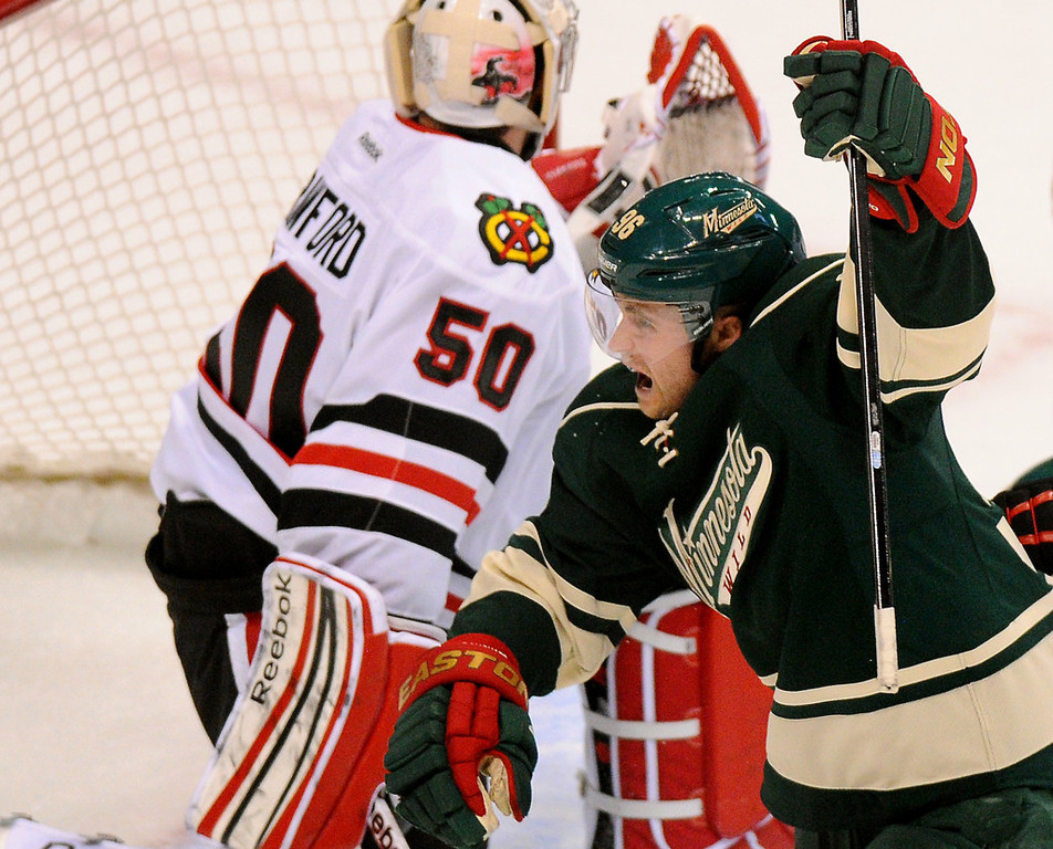 . Minnesota winger Pierre-Marc Bouchard, right, pumps his fist after scoring a tying goal against Chicago goalie Corey Crawford in the first period.  (Pioneer Press: John Autey)