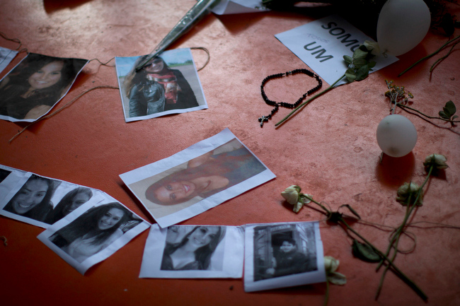 . A makeshift memorial that include pictures of the victims of the Kiss nightclub fatal fire is seen inside the gymnasium where a collective funeral was held a day earlier, in Santa Maria, Brazil, Tuesday, Jan. 29, 2013. A fast-moving fire roared through the crowded, windowless nightclub, early Sunday, killing more than 230 people.  The first funeral services were held Monday for the victims. Most of the dead were college students 18 to 21 years old, but they also included some minors. Almost all died from smoke inhalation. (AP Photo/Felipe Dana)