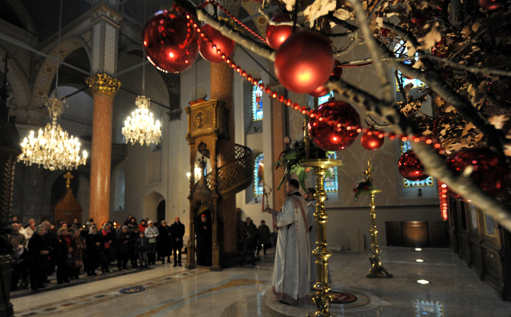 ". Bosnian Orthodox Serbs attend Christmas Mass at the Congregational Church of"" The Mother of God\"" in Sarajevo, on January 7, 2013. Dominantly Orthodox Christians, Bosnian Serbs observe the old \""Julian\"" calendar differing from Catholic and secular, \""Gregorian\"" calendar, established in 16th century. AFP PHOTO ELVIS  BARUKCIC/AFP/Getty Images"