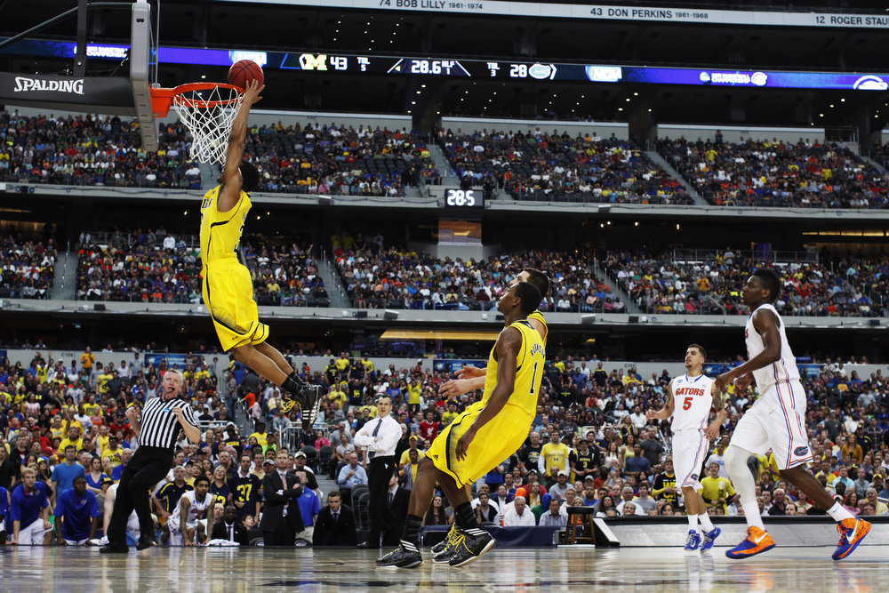 Description of . Trey Burke #3 of the Michigan Wolverines shoots against the Florida Gators in the first half during the South Regional Round Final of the 2013 NCAA Men\'s Basketball Tournament at Dallas Cowboys Stadium on March 31, 2013 in Arlington, Texas.  (Photo by Tom Pennington/Getty Images)