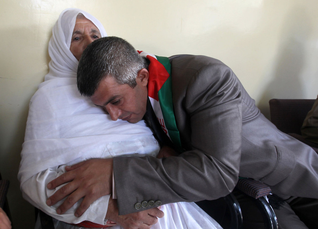 . Palestinian prisoner Mohammed Sawalha hugs his mother after being released from an Israeli jail at his home in the the village of Azmut, in the Israeli occupied Palestinian West Bank on August 14, 2013. Sawalha and his cousin Hosni Sawalha both in their forties, were 17-years -old when incarcerated, and were released alongside 24 other long-serving Palestinian inmates hours before a new round of peace talks with Israel.   JAAFAR ASHTIYEH/AFP/Getty Images