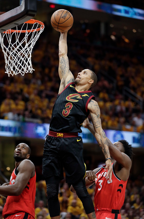 . Cleveland Cavaliers\' George Hill dunks past Toronto Raptors\' OG Anunoby, from England, in the first half of Game 4 of an NBA basketball second-round playoff series, Monday, May 7, 2018, in Cleveland. (AP Photo/Tony Dejak)