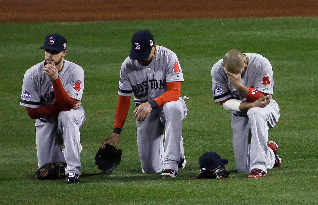 . Boston Red Sox\'s Daniel Nava, left to right, Jacoby Ellsbury and Shane Victorino kneel in the outfield during a pitching change in the seventh inning of Game 3 of baseball\'s World Series against the St. Louis Cardinals Saturday, Oct. 26, 2013, in St. Louis. (AP Photo/David J. Phillip)