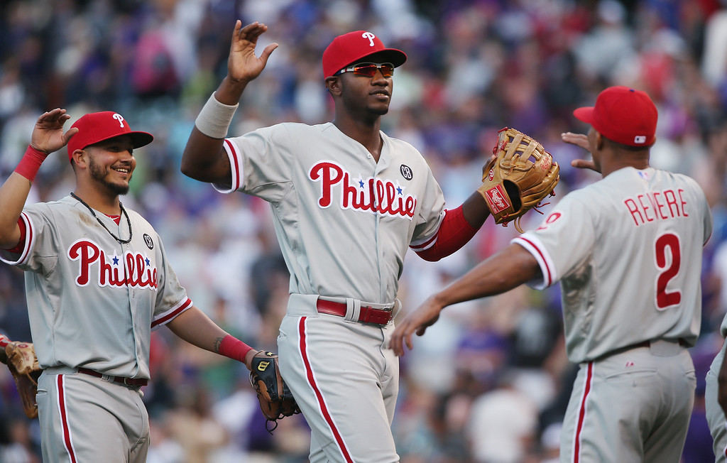 . From left, Philadelphia Phillies third baseman Freddy Galvis, first baseman John Mayberry, Jr., and outfielder Ben Revere celebrate after the Phillies\' 10-9 victory over the Colorado Rockies in a baseball game in Denver on Sunday, April 20, 2014. (AP Photo/David Zalubowski)