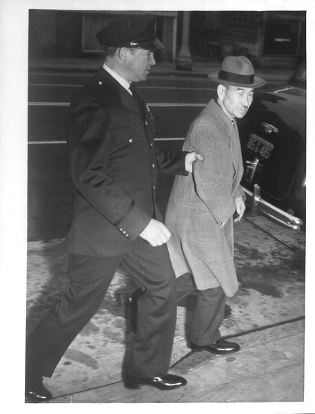 """""""Japanese Roundup -- Many Japanese taken into custody in F.B.I. and police roundup -- Photo shows an official of the San Francisco Japanese Association, Shojiro Hori, is shown being led to car by Officer Bert Nelson.""""--caption on photograph"""