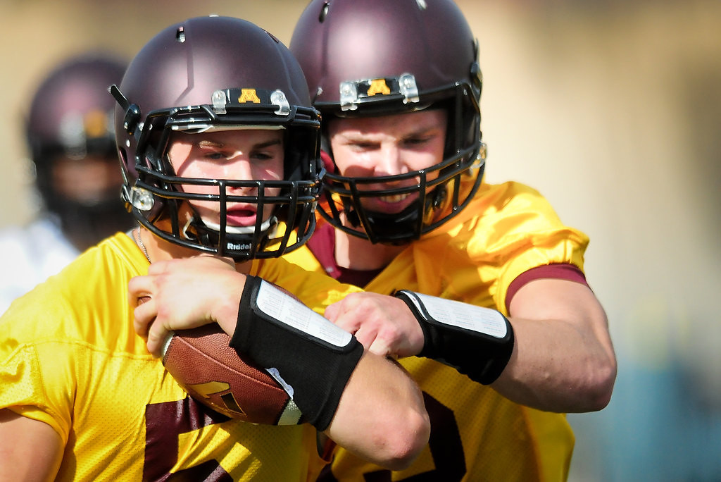. Quarterback Chris Streveler, left, keeps the ball from quarterback Conor Rhoda. (Pioneer Press: Ben Garvin)
