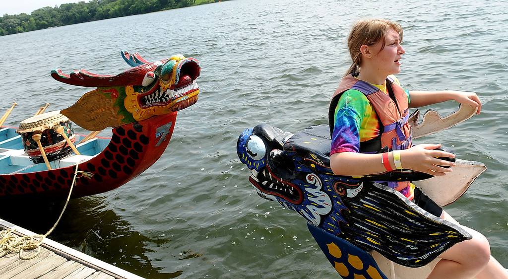 . Sixteen-year-old Miranda Soppeland, flag catcher for Team American Family (Insurance) Flyers, stays steady as crew members board the dragon boat. (Pioneer Press: Sherri LaRose-Chiglo)