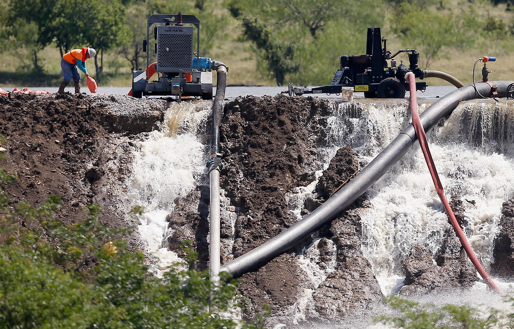 . Workers tend to equipment used to pump water from Padera Lake as water pours over a temporary dam on May 27, 2015 in Midlothian, Texas. Officials feared that the temporary dam on Padera Lake would fail due to recent heavy rains in the area. Areas throughout Texas have experienced flash flooding and numerous deaths due to weeks of heavy rainfall.  (Photo by Tom Pennington/Getty Images)