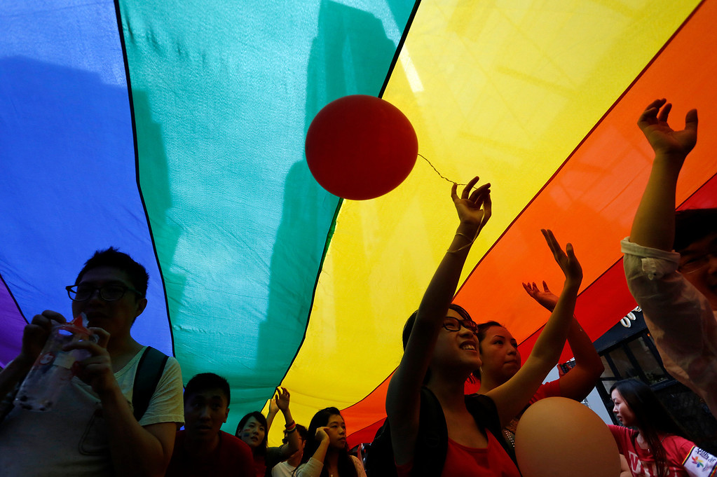 . Participants march as they walk under a rainbow flag, a symbol of the gay rights movement, during a gay rally in Hong Kong Saturday, Nov. 9, 2013. Organizers say thousands of people are taking part in the annual Gay Pride Parade including representatives from more than 50 organizations as well as participants from the mainland and Taiwan, according to government radio. (AP Photo/Vincent Yu)