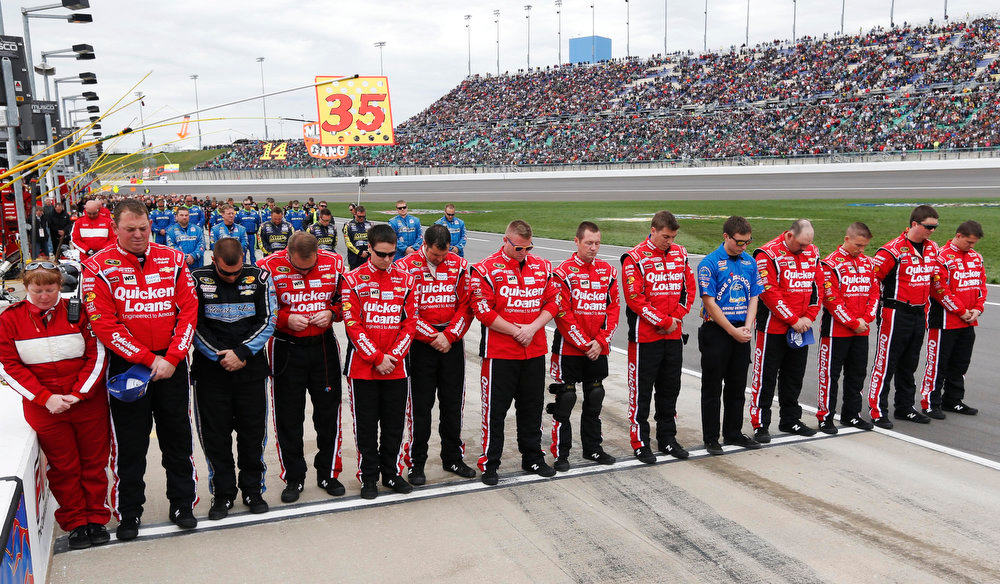 Description of . Crew members for Sprint Cup Series driver Ryan Newman stand for a moment of silence for the victims of the Boston Marathon bombing victim before a NASCAR Sprint Cup series race at Kansas Speedway in Kansas City, Kan., Sunday, April 21, 2013. (AP Photo/Orlin Wagner)